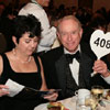 As Gayle Denman looks of the auction booklet, her husband Richard gets ready to bid.